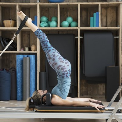 Athletic woman stretches on Pilates reformer with legs in straps.