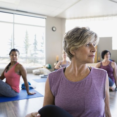 Women practicing seated twist pose in yoga class