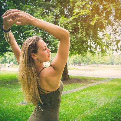 Rear View Of Young Woman Stretching Arms While Standing In Park