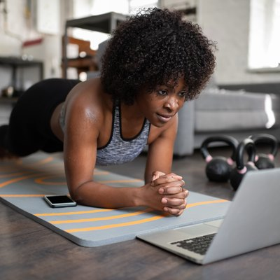 woman holding plank with laptop and water bottle for 30 seconds