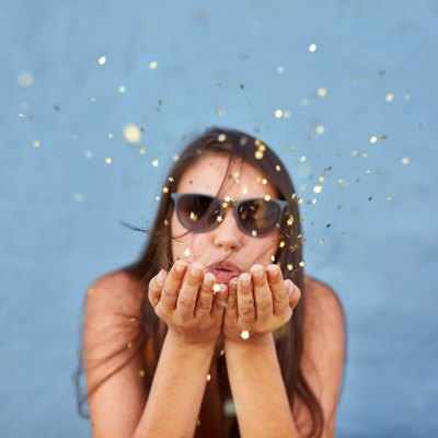 Beautiful woman blowing a burst of magic glitter