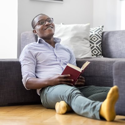 Happy young man sitting on the floor in the living room reading book