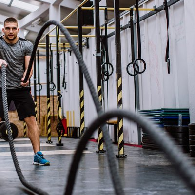 Man Doing Battle Rope Workout in the Gym