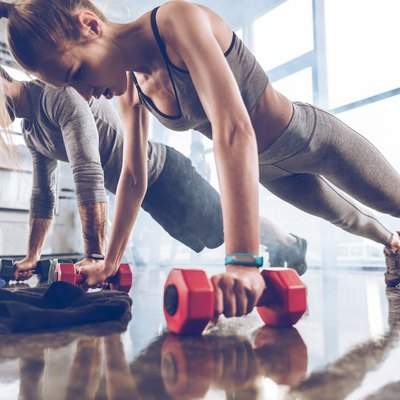 group of athletic young people in sportswear doing push ups with dumbbells at the gym, group fitness concept