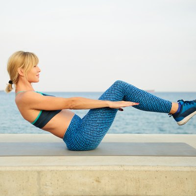 Young athletic woman exercising outdoors: crunch for abdominal strength