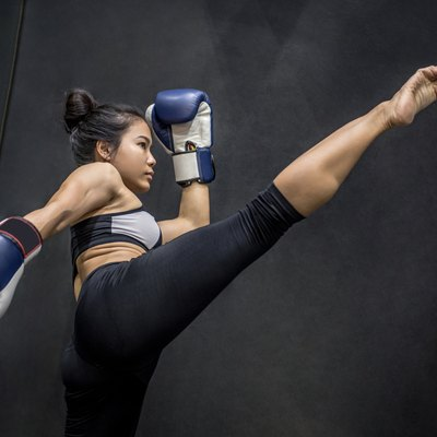Young Asian woman boxer with blue boxing gloves kicking in the exercise gym