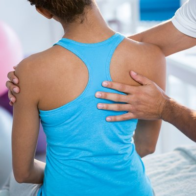 Physiotherapist giving back massage to female patient