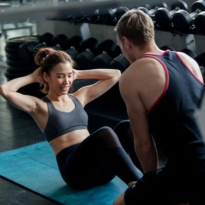 Young Woman doing sit ups at gym . Young athlete doing stomach workout in modern gym. working out together at gym.