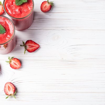 Strawberry smoothie in glass on white background with copy space. Summer drink cocktail. Healthy eating dieting and breakfast concept