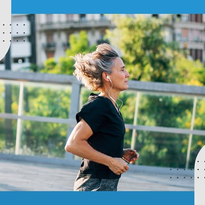 profile view of runner wearing black t-shirt and headphones in a city