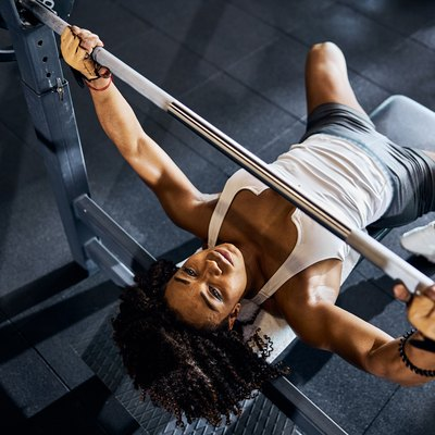 strong black woman doing a barbell bench press