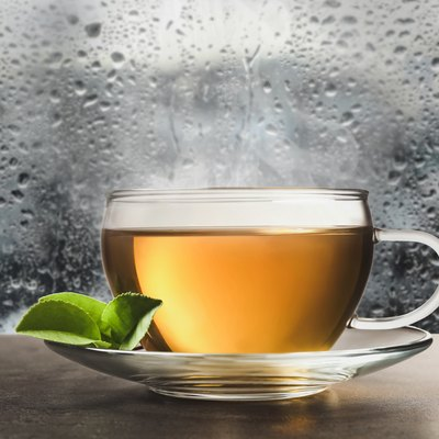 Glass cup of hot green tea near window on rainy day