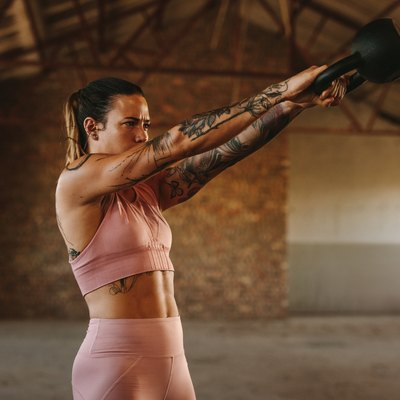 Woman workout with kettle bell inside old warehouse