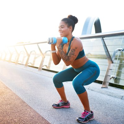 fit woman wearing blue workout leggings and working out with a pair of blue dumbbells outside