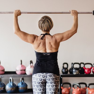 Mature woman training with fitness bar in a gym