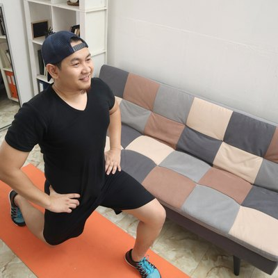 Asian man doing exercise at home while watching online video instruction on laptop, indoor home workout, keep healthy on new normal lifestyle, squat lunges