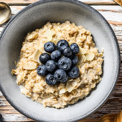 Breakfast oatmeal with  blueberries and almonds.  White wooden background. Top view