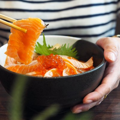 Bowl of sliced grilled Salmon or aburi sashimi top with salmon roe served with wasabi, pickled ginger, seaweed and oba leaf and bowl of mixed salad.