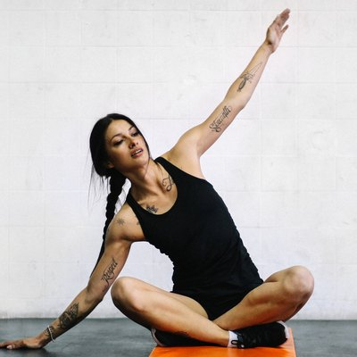 Young woman with tattoos doing yoga mobility exercises