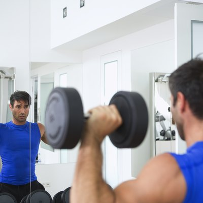 Man doing a dumbbell shoulder press in front of a mirror