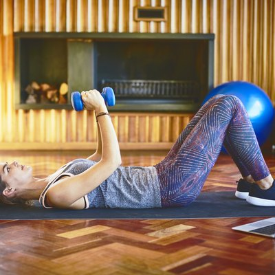 woman lifting dumbbells while lying on floor at home