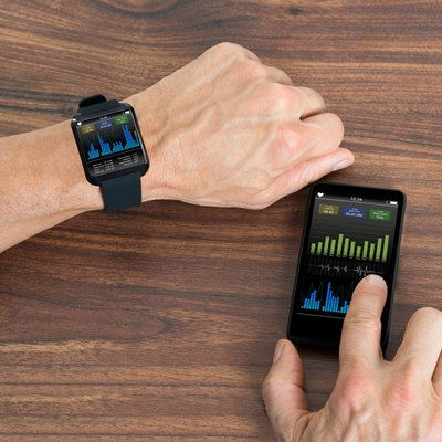 Man With Smartwatch And Cellphone Showing Heartbeat Rate