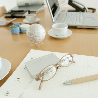 Office with on diary, glasses and coffee cup on desk