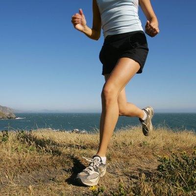 Woman running along coastline,  California,  USA