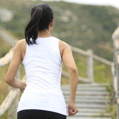 woman runner running at mountain stairs