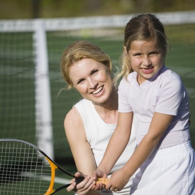 Mother teaching daughter how to play tennis