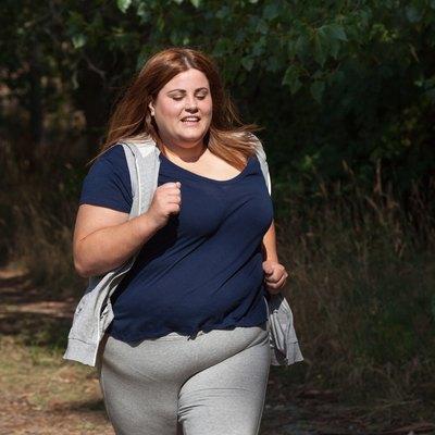 overweight woman running outdoors
