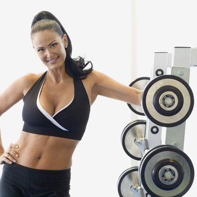 Woman smiling next to weights at health club