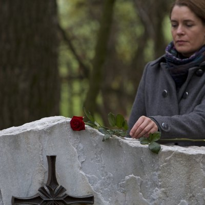 Mature woman placing red rose on gravestone in cemetery