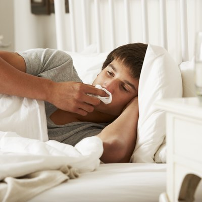 Sick Teenage Boy In Bed At Home