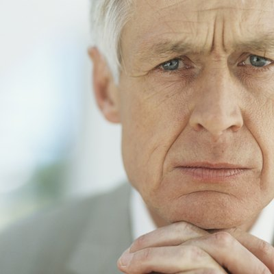 Senior businessman with hands clasped on chin,portrait,close-up