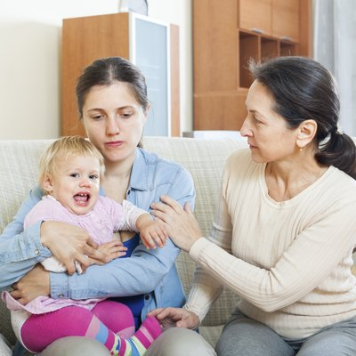 Mature woman comforting  daughter with baby a