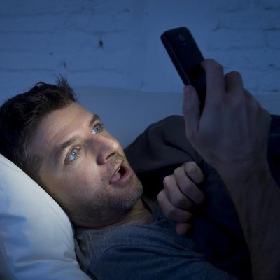 A young man watches porn on his phone in bed.