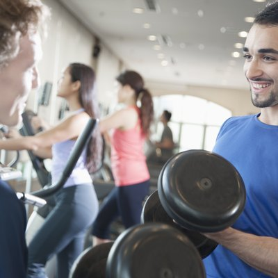 Two young men smiling and lifting weights in the gym