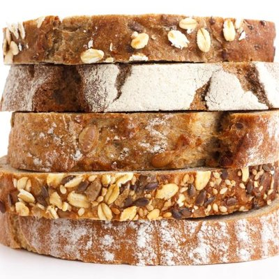 Mixed slices of health breads stacked. White surface.