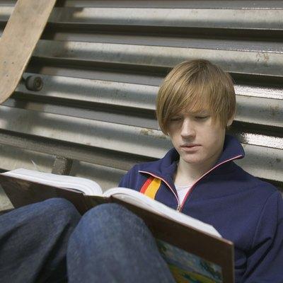Teenage boy reading book outdoors