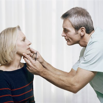 Cosmetic Surgeon Examining a Patients Face