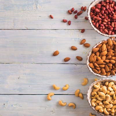Bowls of shelled peanuts almonds and cashew above