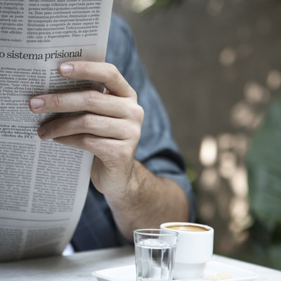 Man reading newspaper outdoors (focus on cups of espresso and water)