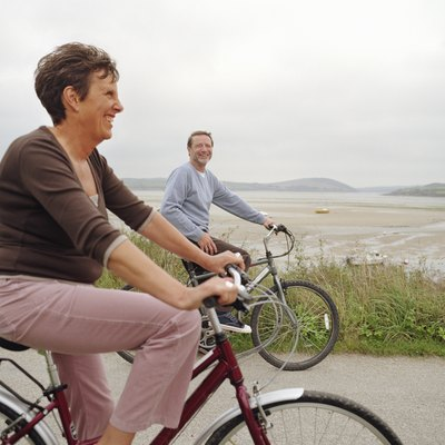 Senior couple riding bicycles by sea, smiling (focus on man)