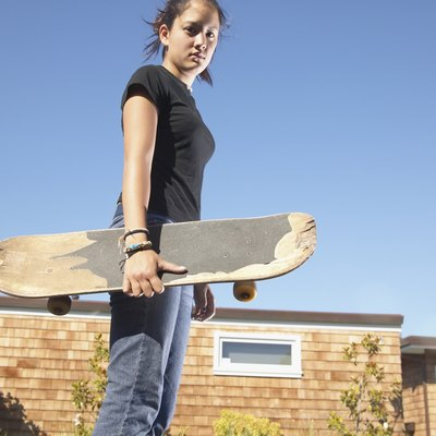Low angle view of a teenage girl holding a skateboard