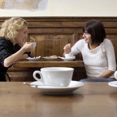Two young women with coffee in cafe, smiling