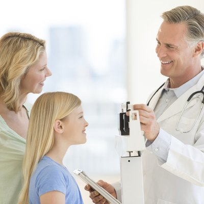 Doctor Examining Girl's Weight While Looking At Woman In Clinic