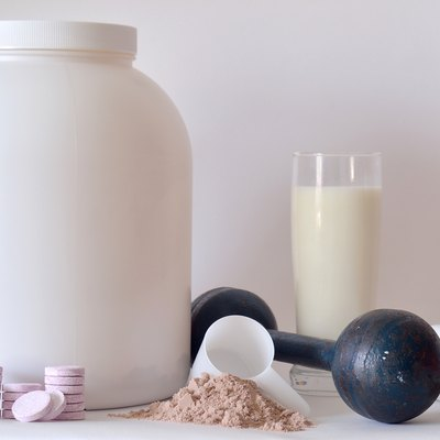 Big jar of protein powder, dumbbell, milk, pills and tablets