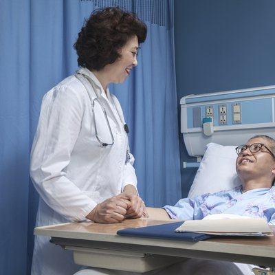 Smiling doctor checking up on a patient lying down in a hospital bed, holding hands