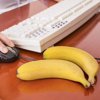 working on a computer  and two banana to eat
